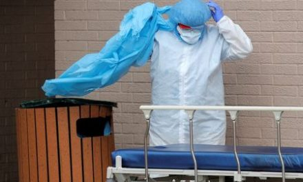 Staff at a NY hospital dump protective gear in outdoor trash can after handling bodies